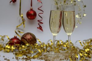 Two champagne glasses sat on a table surrounded by tinsel and baubles
