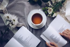 Tea, books and flowers on a table.