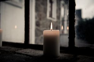 candle representing grief on windowsill
