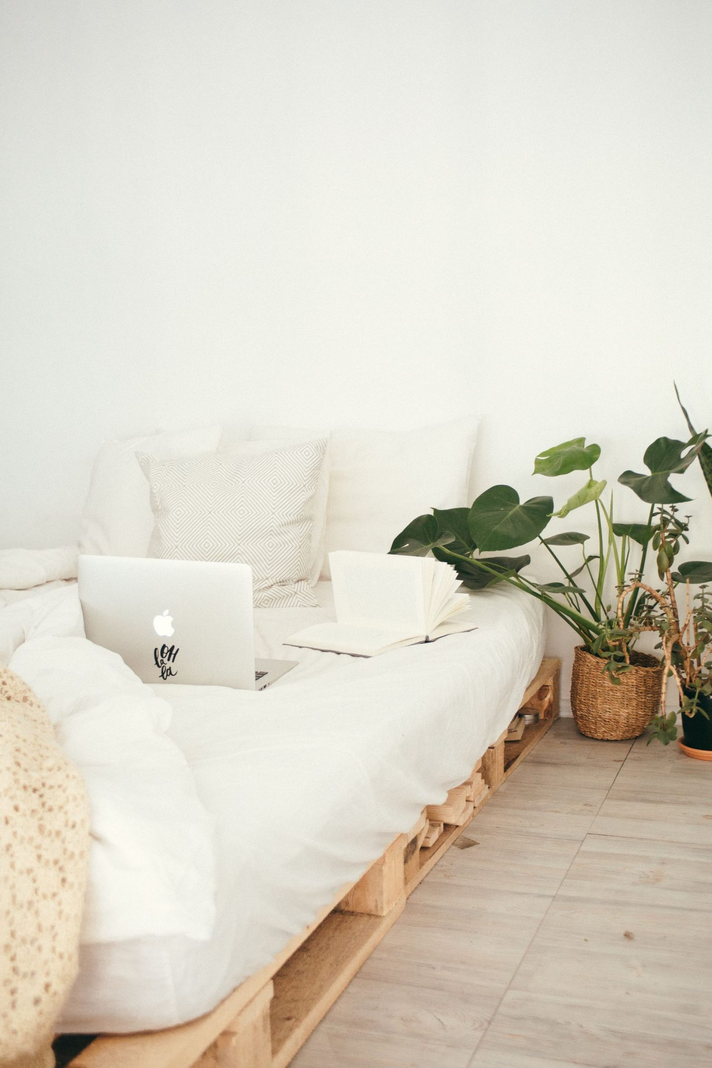 freelancing setup with laptop and book on bed