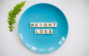 """plate with the words """"weight loss"""" spelled out with scrabble tiles."""